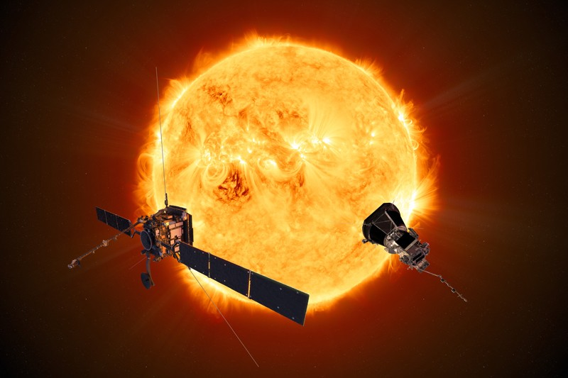 Two spacecraft in front of the Sun.