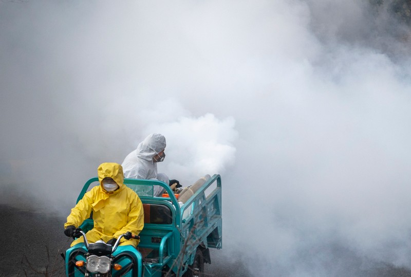Disinfection personnel wearing protective clothing spreading high dense anti-virus spray in China