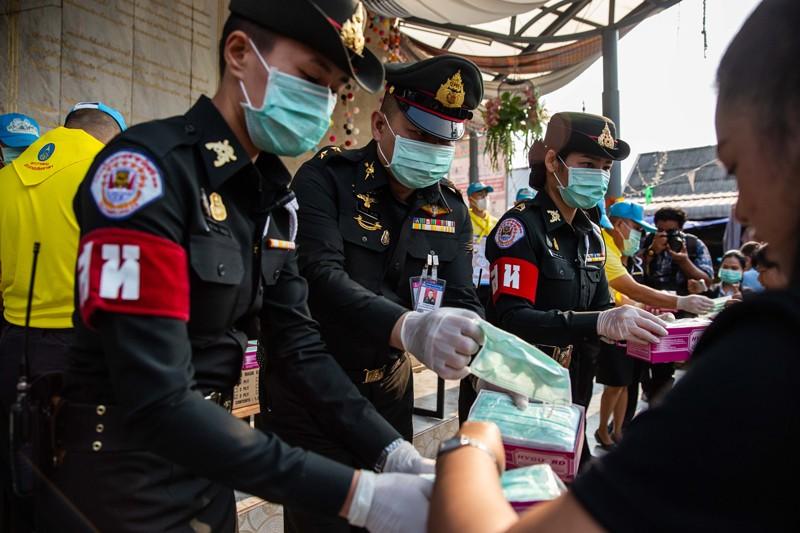 Thai officials handing face masks to pedestrians at a handout station in Bangkok