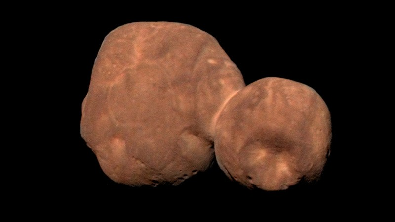 A red rocky object made of two loosely connected lobes, against a black background.