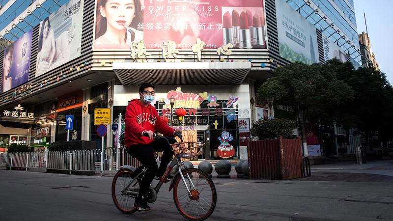 A man wears a protective mask as he ride a bike in the business street on February 13, 2020 in Wuhan.