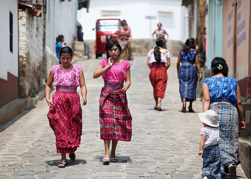 Two women in bright pink tops and skirts walking down a cobbled street.