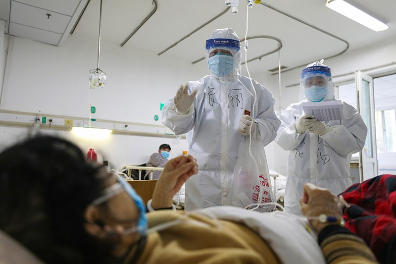 Two medical personnel check on the conditions of a patient with COVID-19 in Jinyintan Hospital