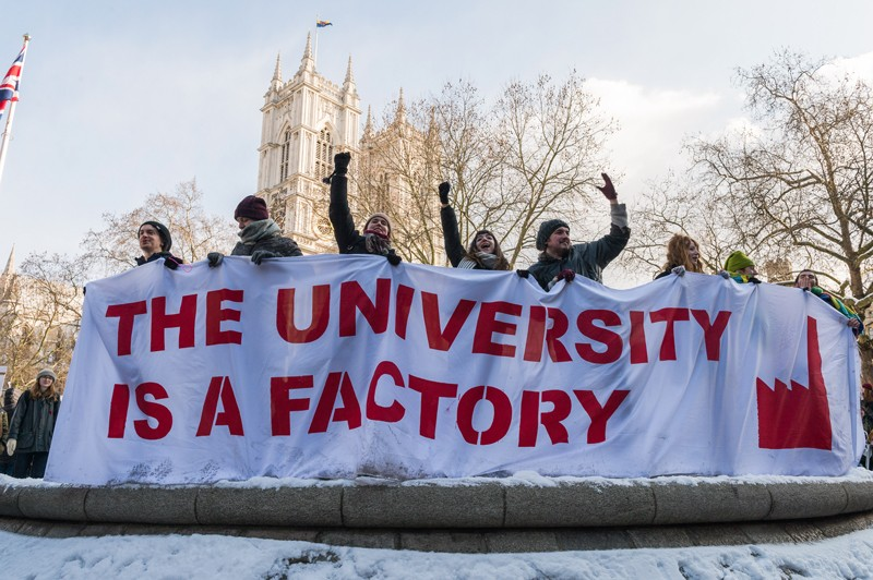 People holding a banner that reads: 'The university is a factory' in the UCU pensions strike, London