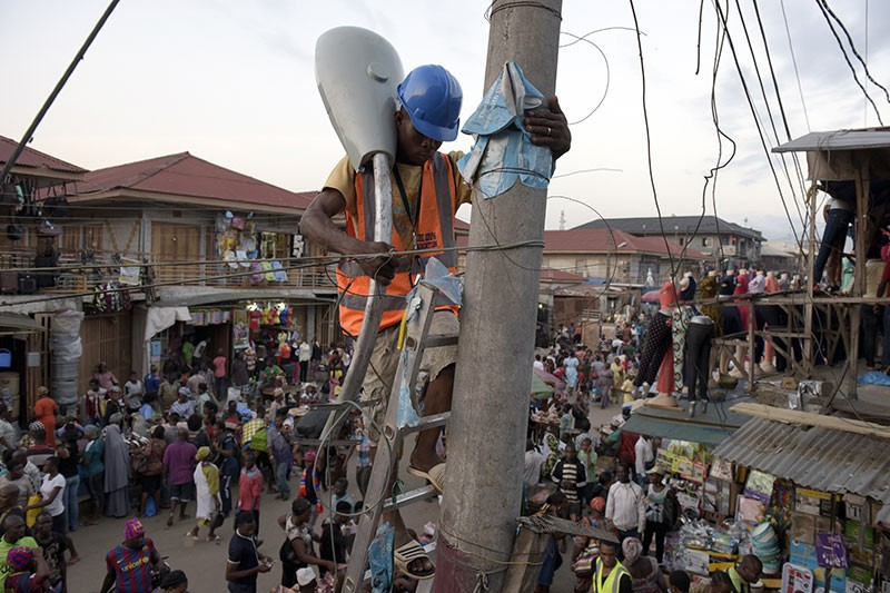 A workman climbs a ladder to install a street lamp in the market area of the Oshodi district in Lagos