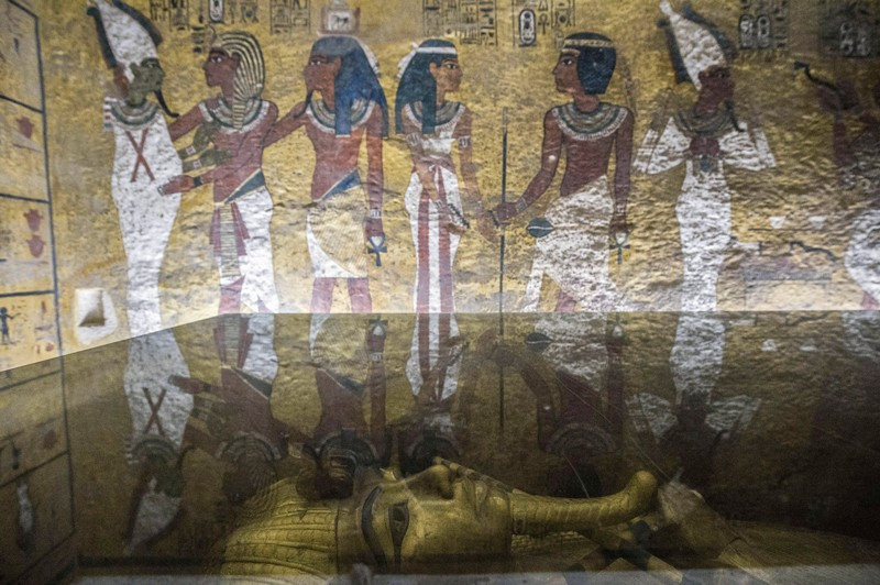 A low                angle of King Tutankhamun's sarcophagus in his burial                chamber, showing a mural on the wall.
