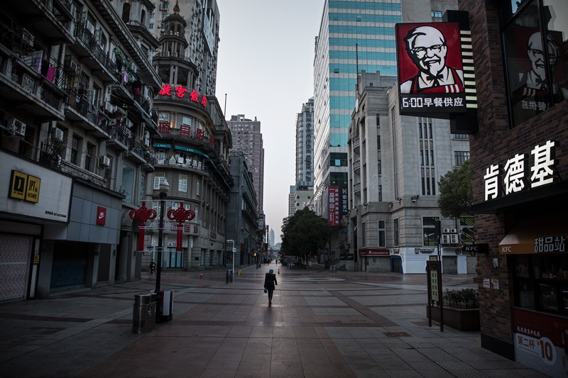 A resident wearing a protective mask walks on an empty business street in Wuhan, China