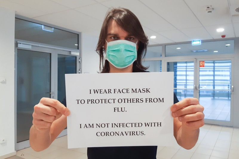 Dr. Piotr Rzymski wearing a face mask and holding a sign that reads: 'I am not infected with coronavirus'