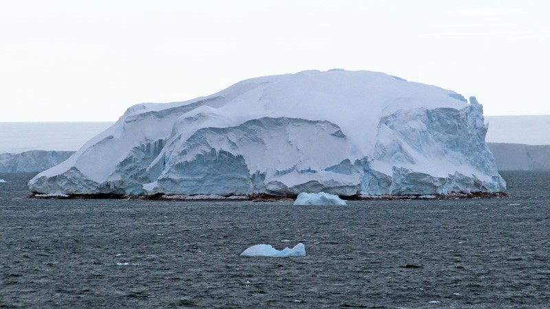 A thin strip of rocks in the sea, covered with a large ice cap.