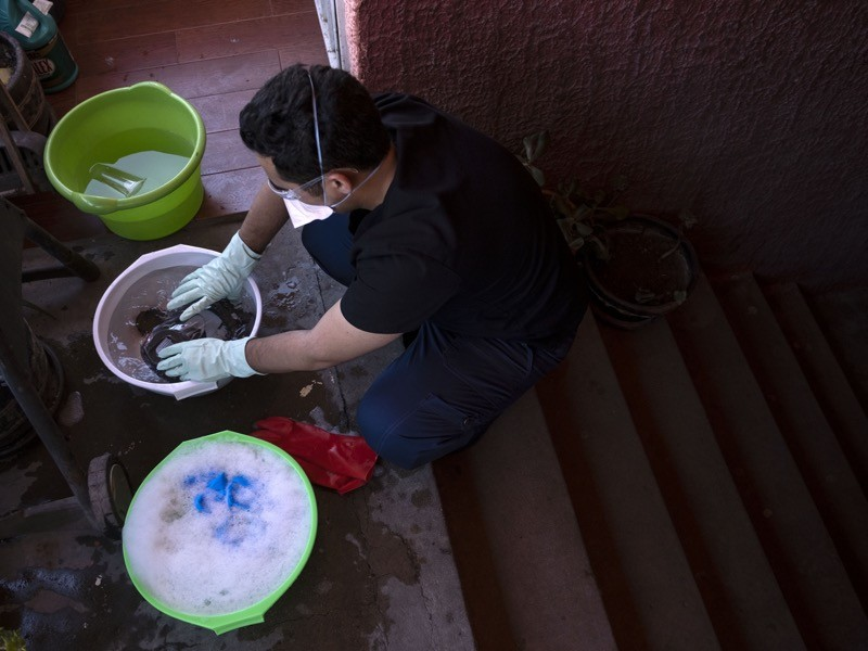 A man in mask and gloves washes his clothes in basins on the steps outside his home.