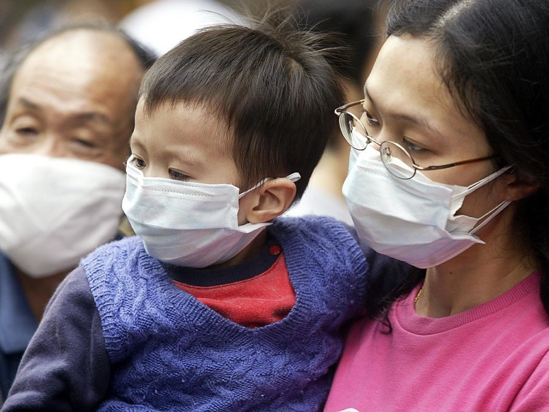 A grandfather, mother and her son wear masks on the street to protect against a deadly pneumonia virus in Hong Kong.