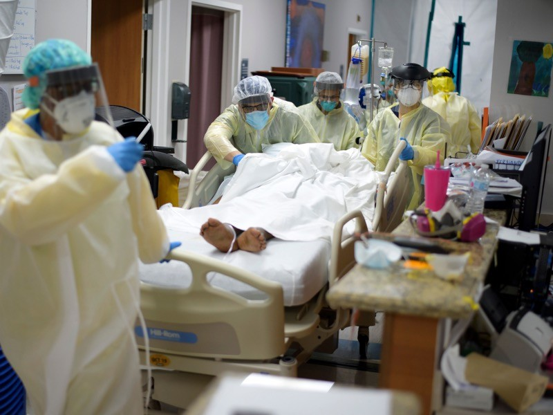Healthcare workers move a patient in the Covid-19 Unit at United Memorial Medical Center in Houston, Texas.