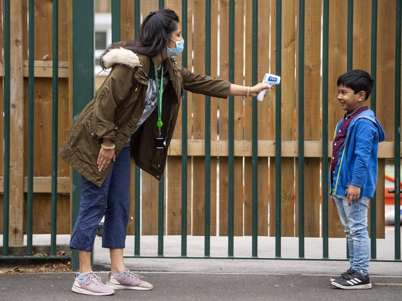 A child has his temperature checked by a teacher before entering Earlham Primary School, UK.