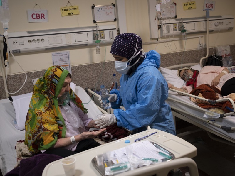 Iranian medical personnel wearing a protective suit takes care of an elderly woman infected with covid.