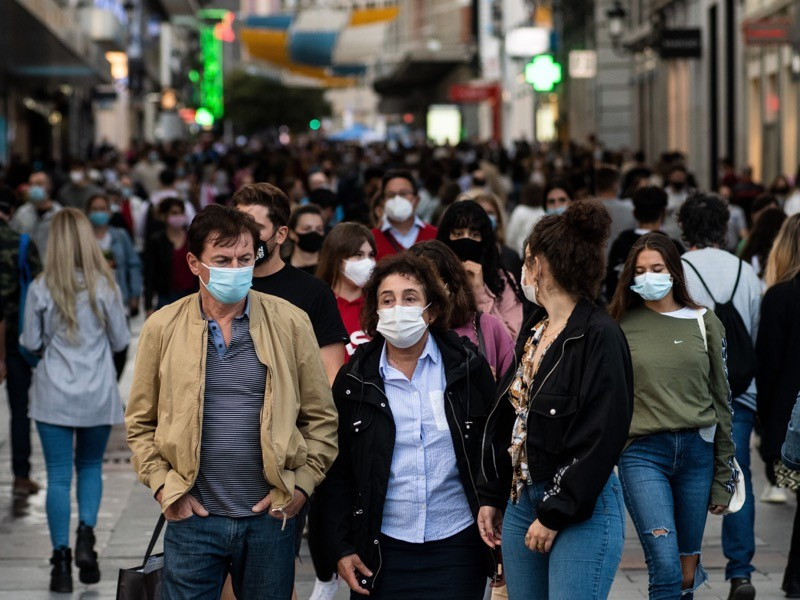 Preciados Street in downtown Madrid crowded with people wearing protective face masks.