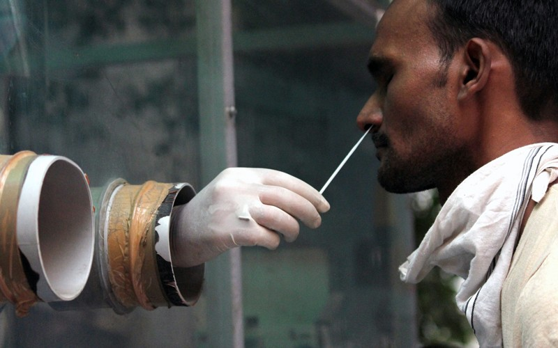 A health worker collects a nasal swab sample from people during weekly market for Covid-19 Rapid Antigen Testing.
