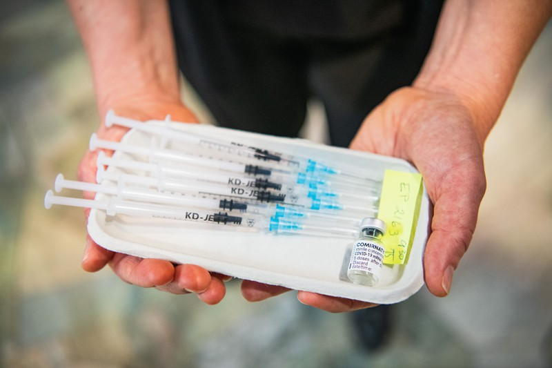 A medial worker holds a tray with syringes and a vial of Pfizer-BioNTech's vaccine