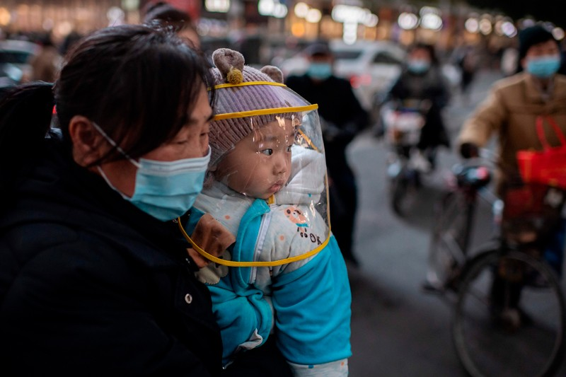 A woman wearing a face mask holds a baby wearing a protective shield.