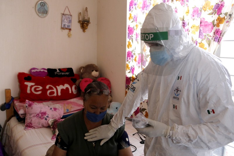 A volunteer doctor checks a woman infected with Covid-19 at home