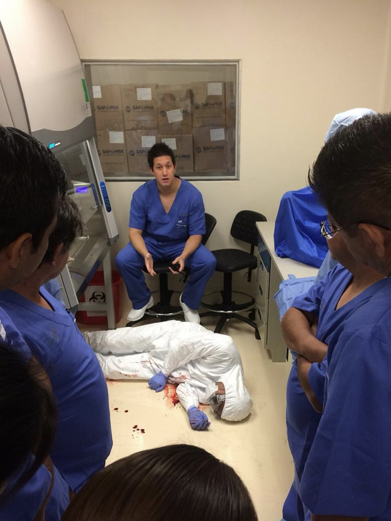 A group watch a demonstration of an accident in a lab with a collapsed figure and Luis Ochoa Carrera