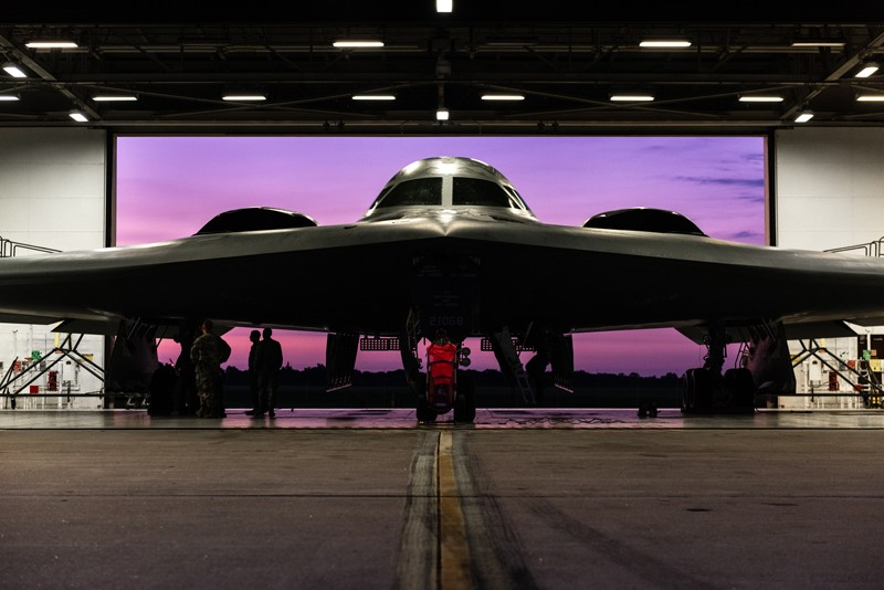 A straight-on view of a B-2 stealth aircraft inside a hanger with a purple sky seen through the door