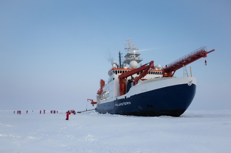 A large ship surrounded by ice. People are walking on the ice floe.