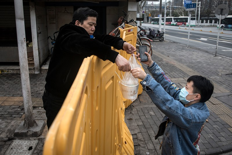 A man wearing a mask sells breakfast to nurses behind a makeshift barricade wall in Wuhan, China.