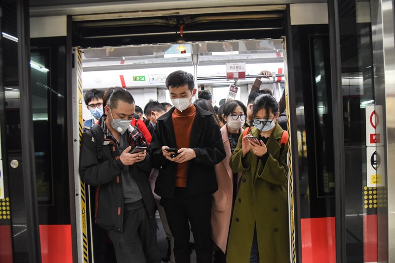 Masked commuters on a subway train, China