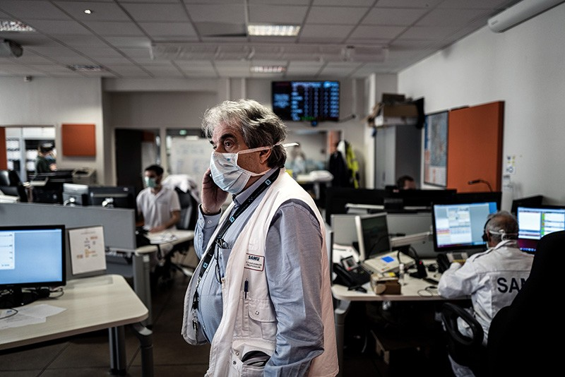 Doctors and health workers wearing masks answer phone calls.