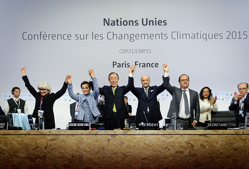 The conference leaders raise hands together after adopting a global warming pact at the COP21 Climate Conference in 2015.