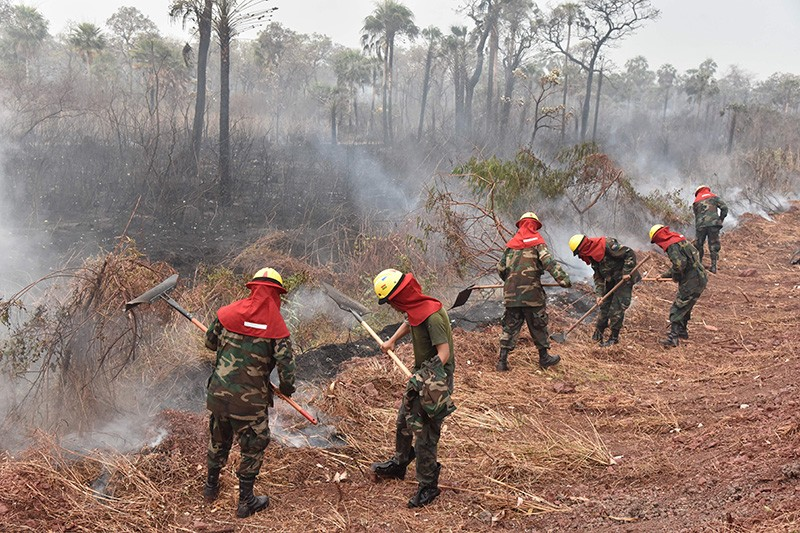 Soldiers attempt to smother smouldering parts of a forest