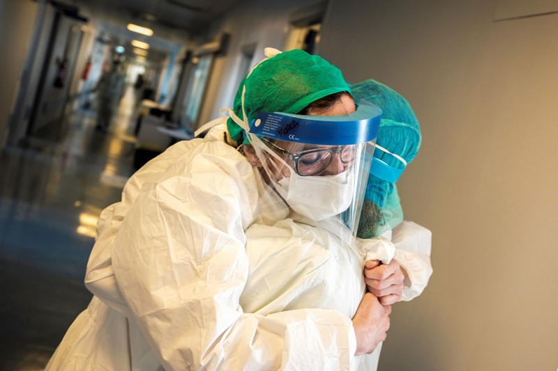 Nurses wearing protective mask and gear embrace in a hospital corridor