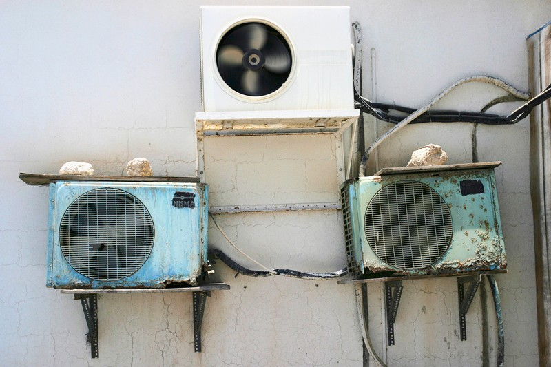 One new and two rusty air conditioning units on the side of a building