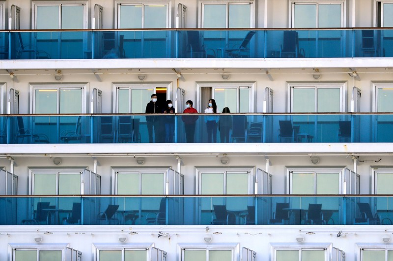 People in facemasks stand on balconies separated by partitions, surrounded by many empty balconies.