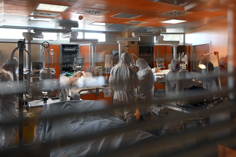 Medical workers in protective gear tend to patients in an intensive care unit.