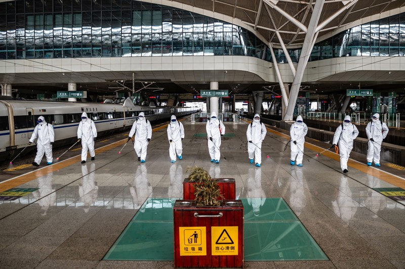 Staff members in protective clothing spray disinfectant at Wuhan Railway Station