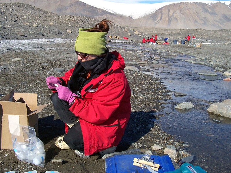 Researchers at the McMurdo Dry Valleys LTER collect stream samples.
