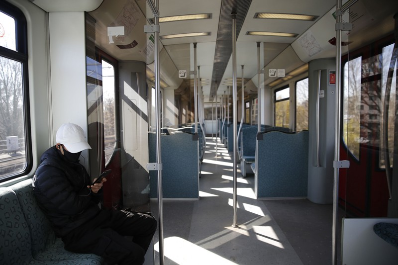 A lone commuter wearing a protective mask checks his phone on an empty train