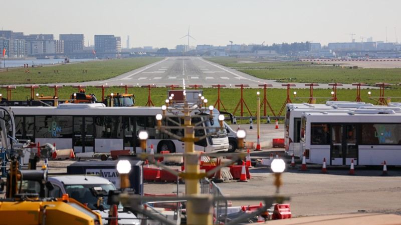 Airport service vehicles parked by an empty runway.