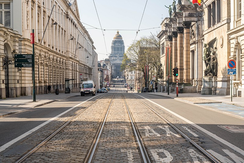 View down a road, featuring tram lines, with a tall building at the end.