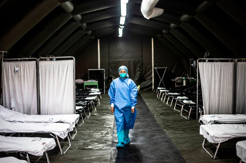 A medical worker in protective clothing and face mask walks through an empty mobile hospital unit in Lima