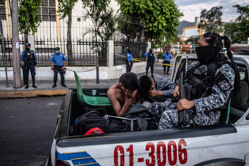 Two young men sit in the back of a police truck with an armed police officer after being arrested in San Salvador
