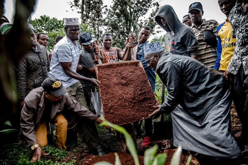 Friends and relatives gather to bury the body of a boy who was allegedly shot by police enforcing curfew in Nairobi
