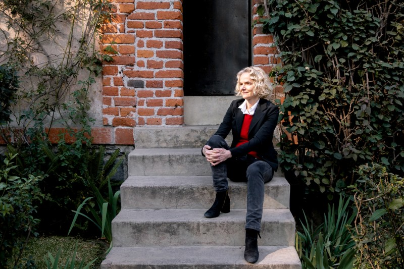 Nora Volkow sits on stones steps in front of a bunker-style door at the Trotsky Museum in Mexico City