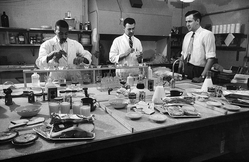 Three physicists in lab testing radioactive fallout on various household goods in 1957.