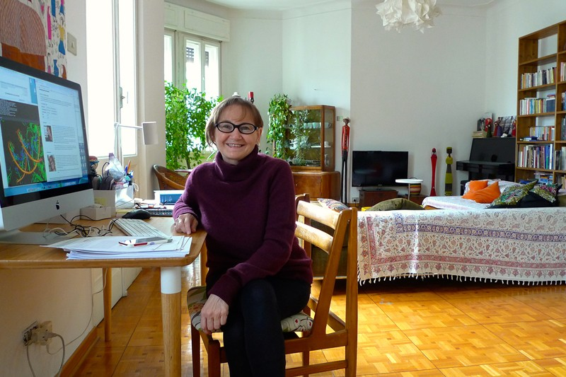A woman sitting at a desk in her living room.