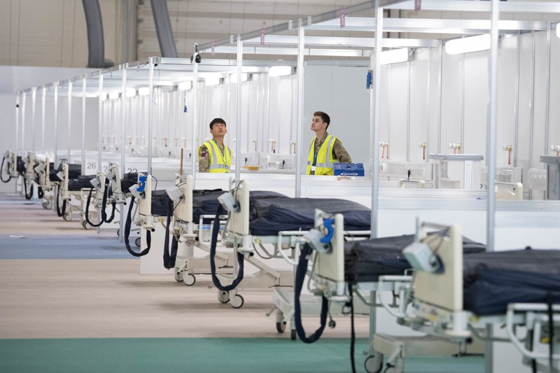 Two men in high-vis vests stand amongst a row of beds in the newly built temporary hospital ward at London ExCel Centre
