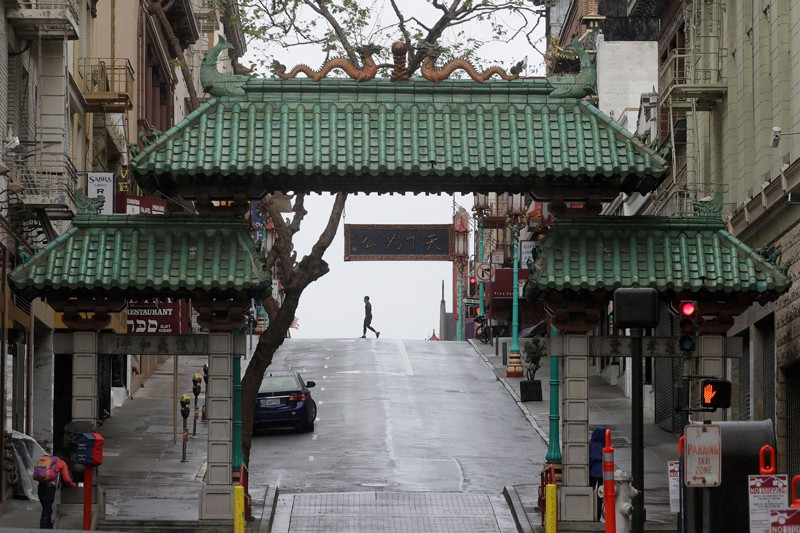 Pedestrian crosses the street behind the Dragon Gate, an entrance to Chinatown in San Francisco
