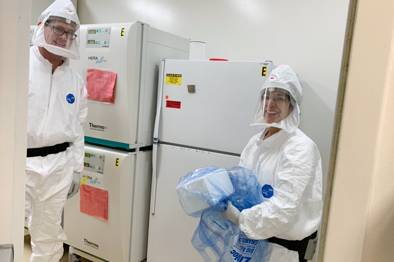 Timothy D Carroll and Lourdes Adamson in protective clothing accepting a patient sample