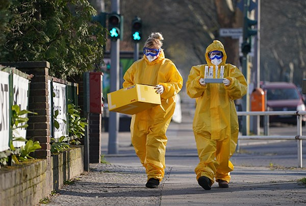 A pair of medical volunteers in full protective outfits who hold samples while walking down a street